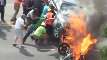 Video : Caught on camera: Biker rescued from under burning car
